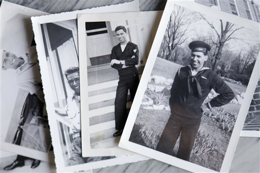 In this Sept. 12, 2011 photo, photographs of Melvin Dwork, taken in 1943 when he was in the Navy, lie on display at his home in New York.