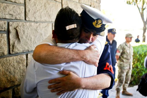 Argentine Navy officials embrace inside the Mar de Plata Naval Base after Argentina's Navy announced that a sound detected during the search for the missing ARA San Juan submarine is consistent with that of an explosion, in Mar de Plata, Argentina, Thursd