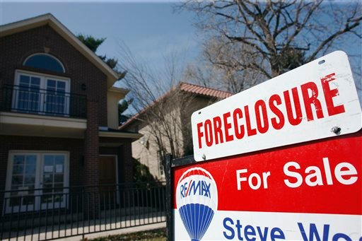 In this April 4, 2010 file photo, a foreclosure sign sits atop a for sale sign in front of a single-family home tops the for sale sign in Denver. (AP Photo/David Zalubowski, File)