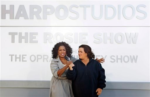 "Rosie O'Donnell, right, and Oprah Winfrey speak to the media after the unveiling of a new sign outside Harpo Studios welcoming ""The Rosie Show,"" to the studio Sept. 15, 2011, in Chicago. (AP Photo/M. Spencer Green)"