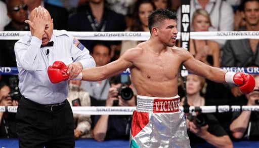 Referee Joe Cortez motions that Victor Ortiz, right, delivered a head butt to Floyd Mayweather in the fourth round during a WBC welterweight title fight.