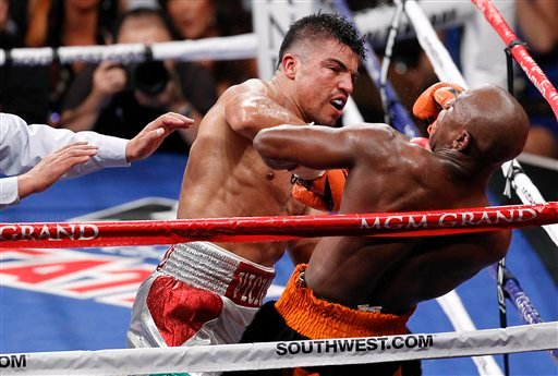 Floyd Mayweather rears back on the ropes after a head butt by Victor Ortiz, left.