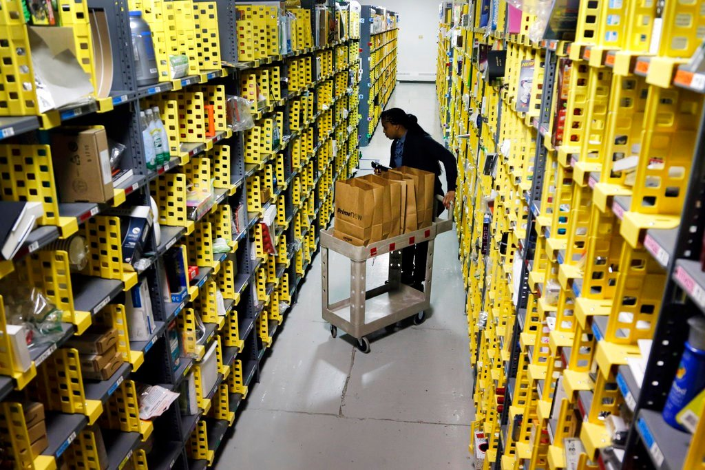 FILE - In this Tuesday, Dec. 22, 2015, file photo, Amazon Prime employee Alicia Jackson hunts for items at the company's urban fulfillment facility that have been ordered by customers, in New York. (AP Photo/Mark Lennihan, File)