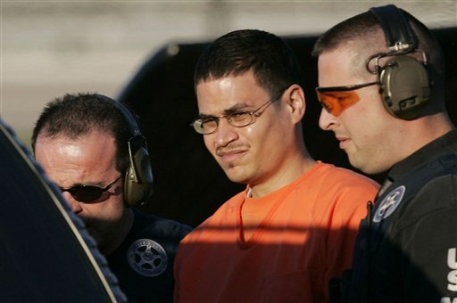 In this Jan. 5, 2006 file photo, Jose Padilla, center, is escorted to a waiting police vehicle by federal marshals near downtown Miami. (AP)