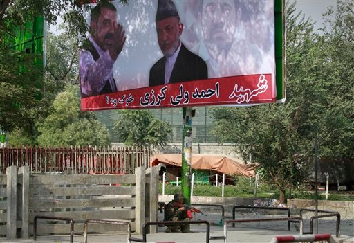 An Afghan soldier takes position under a huge poster of Afghan President Hamid Karzai with his late brother Ahmad Wali Karzai, during a gun battle with militants in Kabul, Afghanistan on Tuesday, Sept. 13, 2011.