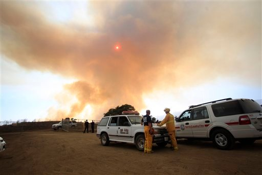 Fire officials watch the growing smoke from a brush fire that started on Camp Pendleton when a Marine helicopter crashed Monday Sept. 19, 2011 in De Luz, Calif.
