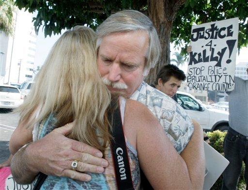 Ron Thomas, father of Kelly Thomas, embraces a supporter before Orange County, Calif., District Attorney Tony Rackauckas announces that two police officers will be charged in the death of his son, Kelly Thomas, a mentally ill homeless man.