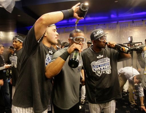 Yankees' Jesus Montero, left, Robinson Cano, center, and Eduardo Nunez, right, celebrate after the Yankees clinched the AL East title with a 4-2 win over the Rays in the second game of a baseball doubleheader Sept. 21, 2011. (AP Photo/Frank Franklin II)