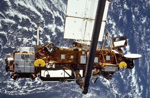 In this image provided by NASA this is the STS-48 onboard photo of the Upper Atmosphere Research Satellite (UARS) in the grasp of the RMS (Remote Manipulator System) during deployment, from the shuttle in September 1991.