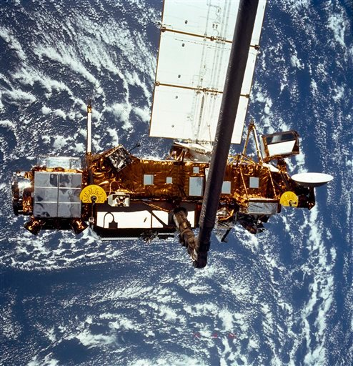 In this file image provided by NASA this is the STS-48 onboard photo of the Upper Atmosphere Research Satellite (UARS) in the grasp of the RMS (Remote Manipulator System) during deployment, from the shuttle in September 1991. (AP)