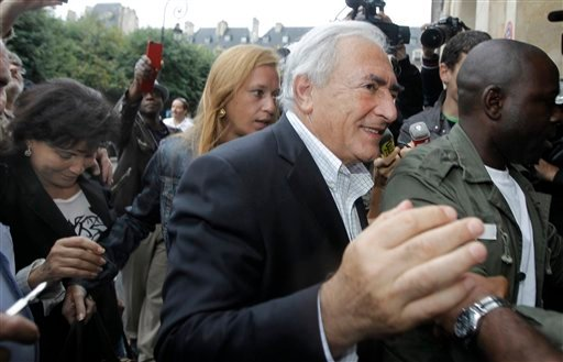 Dominique Strauss-Kahn, former head of the International Monetary Fund, followed by his wife, Anne Sinclair, far left, arrives at his home in Paris, France, Sunday, Sept. 4, 2011.