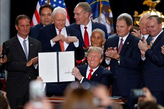 President Donald Trump holds up a signed proclamation to shrink the size of Bears Ears and Grand Staircase Escalante national monuments at the Utah State Capitol.