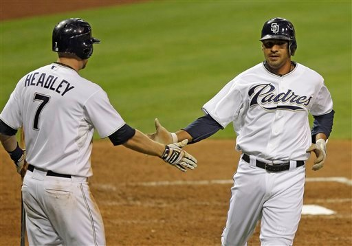 San Diego Padres' Jesus Guzman is congratualted by Chase Headley, left, after scoring from second on a hit by Cameron Maybin during the sixth inning of a baseball game against the Chicago Cubs, Monday, Sept. 26, 2011, in San Diego. (AP Photo/Lenny Ignelzi