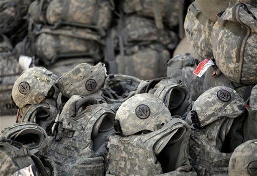 In this Tuesday, Aug. 2, 2011 photo, helmets and body armor are are stacked and ready to go outside the passenger terminal at Sather Air Base in Baghdad, Iraq.