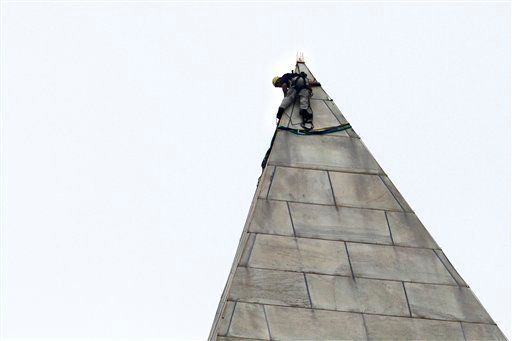 A man attaches rigging to the top of the Washington Monument on the National Mall, in Washington, Tuesday, Sept. 27, 2011, before engineers rappeled down the sides of the monument to survey the extent of damage sustained to the monument .