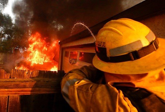 A Los Angeles County firefighter puts water a burning house in a wildfire in the Lake View Terrace area of Los Angeles.