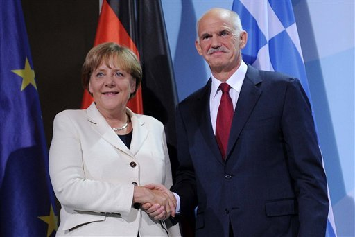 German Chancellor Angela Merkel, left, and the Prime Minister of Greece, Georgios Papandreou, right, shake hands prior to a dinner at the chancellery in Berlin, Germany, Tuesday, Sept. 27, 2011.