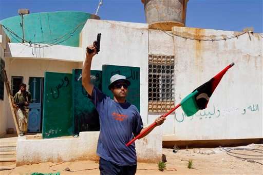A Libya fighter celebrates as revolutionary fighters enter a Moammar Gadhafi political office next to a police station as they take control of Muammar Qaddafi loyalists villages in the desert some 730 km south of Tripoli.