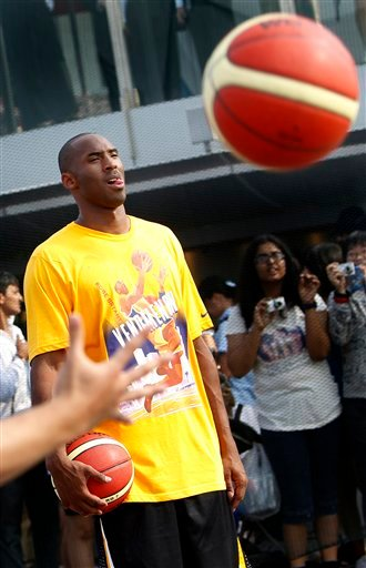 Los Angeles Lakers superstar Kobe Bryant, center, reacts before coaching a basketball clinic on Saturday Sept. 17, 2011 in Singapore.