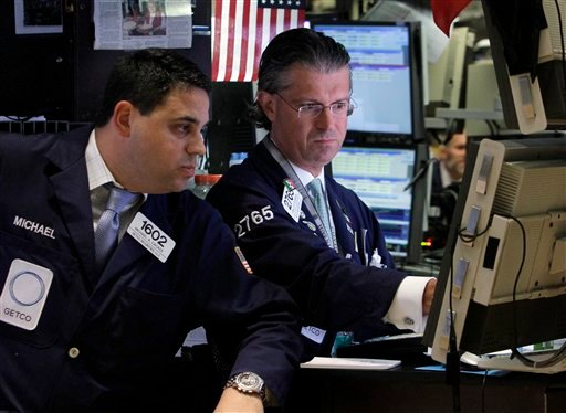 Specialists Michael Cacace, left, and Donald Civitanova work on the floor of the New York Stock Exchange Monday, Aug. 29, 2011.