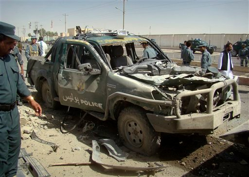 An Afghan police officer, left, looks at a police vehicle damaged in a suicide attack in Lashkar Gah, Helmand province, Afghanistan, Tuesday, Sept. 27, 2011.