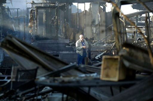 Dick Marsala looks through debris from his destroyed home after a wildfire roared through the Rancho Monserate Country Club Friday, Dec. 8, 2017, in Bonsall, Calif. The wind-swept blazes have forced tens of thousands of evacuations and destroyed dozens of