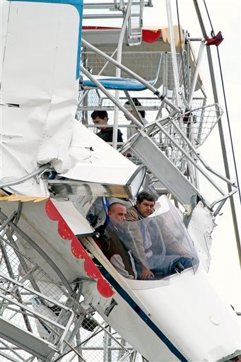 Two men and their ultra-light plane hang from a Ferris wheel while two children sit in a carriage near the top of the ride at a country festival at Old Bar, Australia, Saturday, Oct. 1, 2011. The four people were trapped in the tangled wreckage for hours