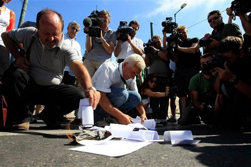 Employees from public entities which Greek government plans to close or merge, burn emergency tax notices outside the parliament in Athens, Wednesday, Sept. 21, 2011. (AP)
