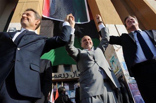 French President Nicholas Sarkozy, left, Libya's NTC leader Mustafa Abdul-Jalil, center, and British Prime Minister David Cameron, right, gesture during their visit to Benghazi, Libya, Thursday, Sept. 15, 2011.