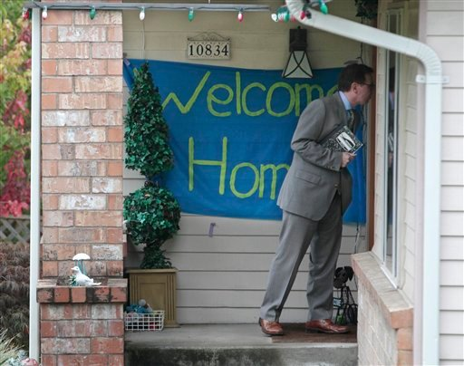 """A reporter knocks on the door where a """"welcome home"""" sign is posted at the home of Curt Knox for his daughter Amanda Knox on her expected arrival later in the day Tuesday, Oct. 4, 2011, in Seattle."""
