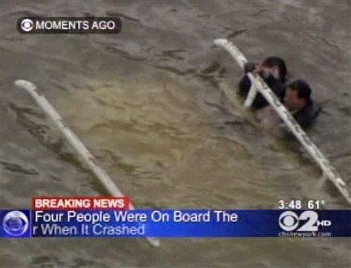 In this frame grab image taken from WCBS-TV, survivors cling to the bottom of a helicopter after it inverted following a crash in the East River in New York, Tuesday Oct. 4, 2011.
