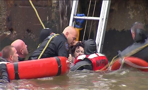 In this frame taken from video, divers pull a woman from the water onto a dock on the East River after the helicopter she was in crashed, Tuesday, Oct. 4, 2011, in New York. (AP Photo/WPIX11-TV News)