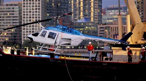 A helicopter that crashed into the East River in New York is hoisted from the water Tuesday, Oct. 4, 2011. (AP Photo/Craig Ruttle)