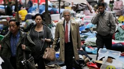 Commuters walk through Zuccotti Park in the financial district where Occupy Wall Street protestors are encamped in New York, Tuesday, Oct. 4, 2011. (AP Photo/Seth Wenig)