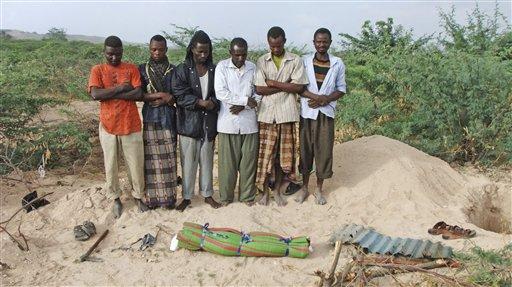 Somali men from southern Somalia offer funeral prayers for a dead child in Mogadishu, Somalia, Saturday, Sept. 10, 2011.