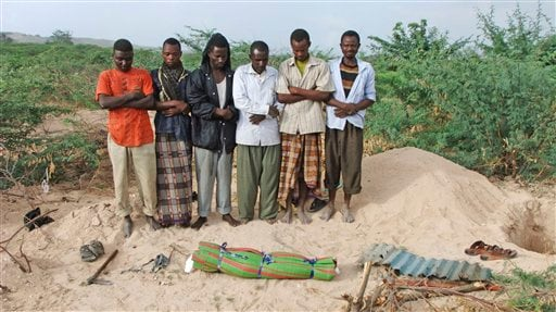 Somali men from southern Somalia offer funeral prayers for a dead child in Mogadishu, Somalia, Saturday, Sept. 10, 2011.