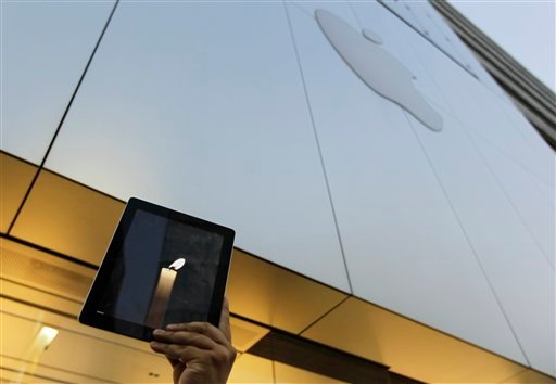 An Apple computer fan raises his iPad displaying candle graphics during a candle light vigil to pay tribute to Steve Jobs. (AP Photo/Hiro Komae)