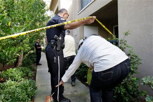 A San Jose police officer helps out the neighbor of a shooting suspect at his apartment in San Jose, Calif., Wednesday, Oct. 5, 2011. (AP Photo/Paul Sakuma)