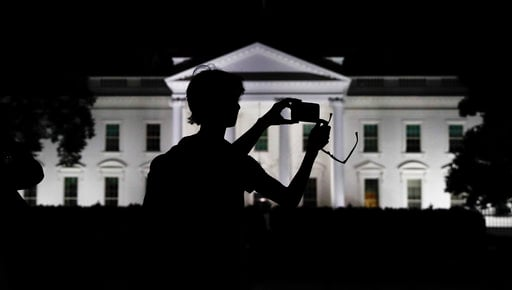 FILE - In this Aug. 25, 2017, file photo, a tourist takes a photo from Pennsylvania Avenue of the illuminated White House in Washington. (AP Photo/Carolyn Kaster, File)