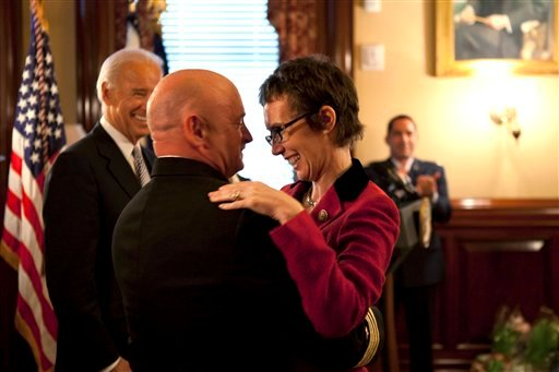 In this image released by the White House, Navy Capt. Mark Kelly hugs his wife Rep. Gabrielle Giffords, D-Ariz., after he received the Legion of Merit from Vice President Joe Biden during Kelly's retirement ceremony.