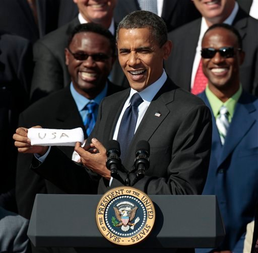 President Barack Obama holds up a headband given to him by former quarterback Jim McMahon, as he honors the 1985 Super Bowl XX Champions Chicago Bears football team.