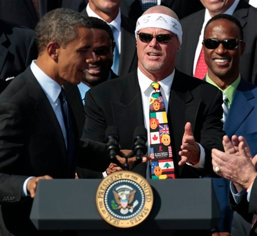 President Barack Obama, left, looks towards quarterback Jim McMahon, right, wearing headband.