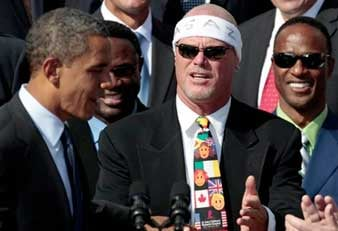 President Barack Obama stands at the podium with head coach Mike Ditka, left, and defensive coordinator Buddy Ryan, third left, as he honors the 1985 Super Bowl XX Champions Chicago Bears football team.