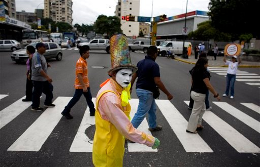 A mime walks alongside pedestrians as they cross a street in Caracas, Venezuela, Friday Oct. 7, 2011. (AP)