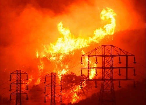 Flames burn near power lines in Sycamore Canyon near West Mountain Drive in Montecito, Calif.