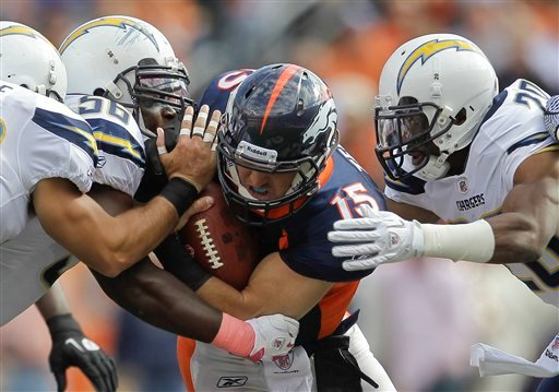 Denver Broncos quarterback Tim Tebow (15) is hit by San Diego Chargers inside linebacker Donald Butler (56) and San Diego Chargers cornerback Antoine Cason (20) in the second quarter during an NFL football game, Sunday, Oct. 9, 2011, in Denver. (AP Photo)