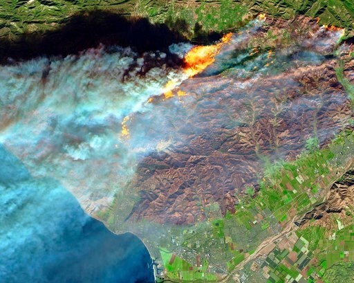 This Thursday, Dec. 7, 2017 false-color image from the European Space Agency's Sentinel-2 satellite via NASA, shows a brown burn scar from the Thomas fire north of the city of Ventura, Calif., at bottom center. AP