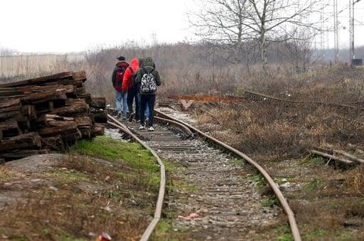 Migrants walk on train tracks near the western Serbian town of Sid, near Serbia's border with European Union member Croatia, Monday, Dec. 18, 2017. (AP Photo/Darko Vojinovic)
