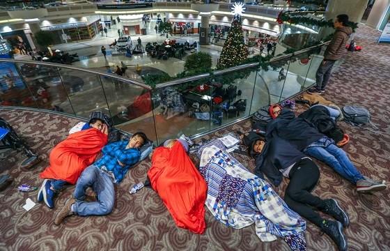 Travelers sleep in the atrium at Hartsfield-Jackson International Airport.