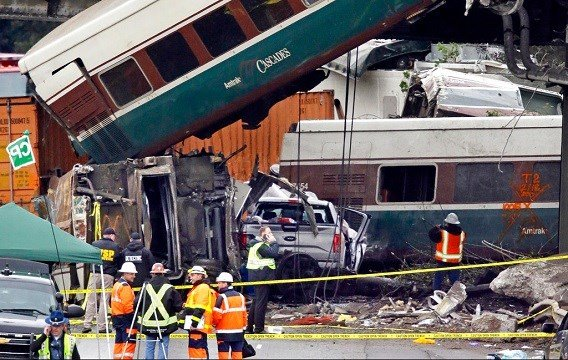 Cars from an Amtrak train that derailed above lay spilled onto Interstate 5 alongside smashed vehicles.